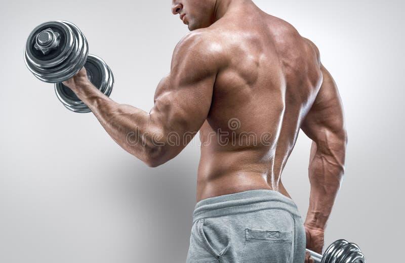 Accione al hombre atlético en el entrenamiento que bombea para arriba muscles con pesas de gimnasia foto de archivo libre de regalías