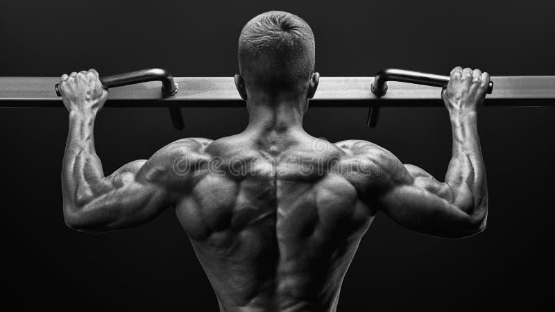 Accione al individuo muscular del culturista que hace pullups en gimnasio Hombre de la aptitud imagen de archivo libre de regalías