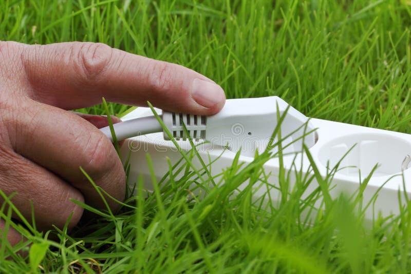 Accione la tira que miente en la hierba y la mano foto de archivo libre de regalías