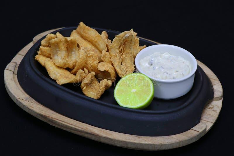 Acciughe fritte nel grasso bollente con la salsa di tartaro ed il cuneo della calce immagine stock