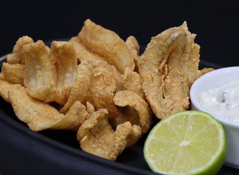 Acciughe fritte nel grasso bollente con la salsa di tartaro ed il cuneo della calce in un piatto servire fotografia stock