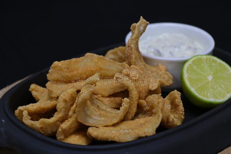 Acciughe fritte nel grasso bollente con la salsa di tartaro ed il cuneo della calce in un piatto servire immagine stock libera da diritti