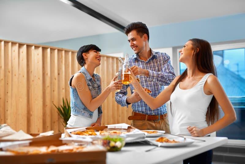 acclamazioni Amici felici che incoraggiano le bottiglie di birra all'interno Partito cele fotografie stock