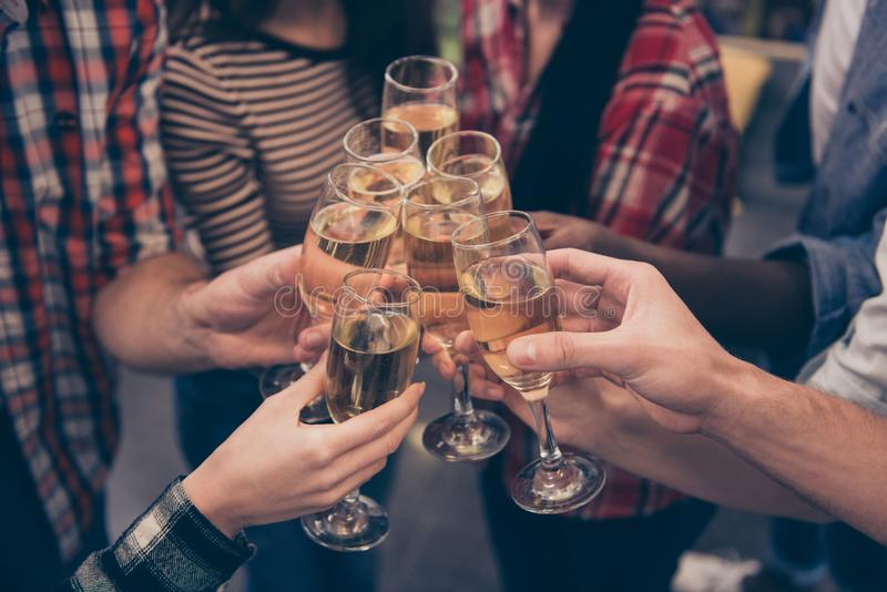 Acclamazioni! Chiuda su dei migliori amici tintinnanti con i bicchieri di vino che si tengono per mano la celebrazione scintillan immagine stock