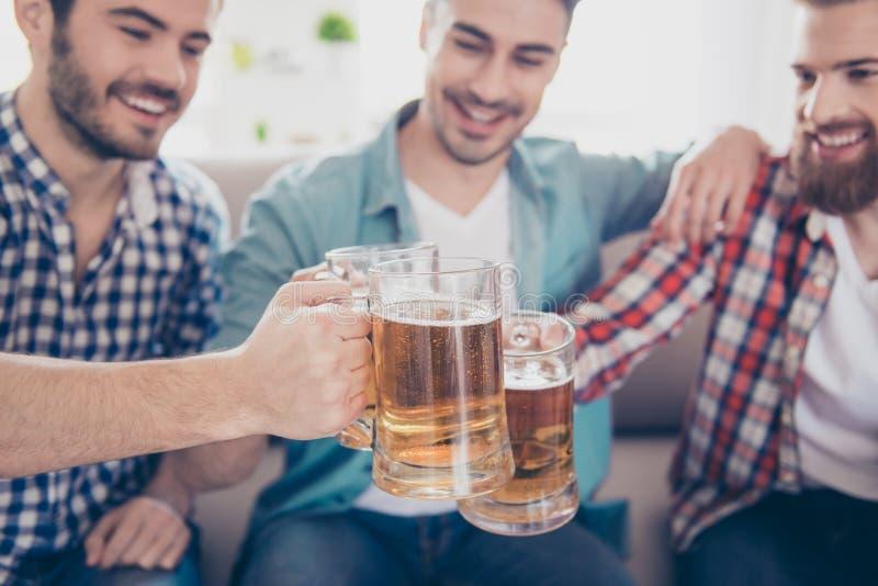 Acclamazioni! Chiuda sulla foto potata degli uomini bei felici che celebrano fotografia stock