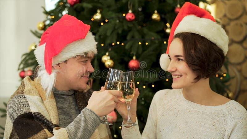 Acclamazioni, fine su per le coppie amorose in vetri tintinnanti del cappello di Santa Claus di shampagne sull'albero di Natale d fotografia stock libera da diritti
