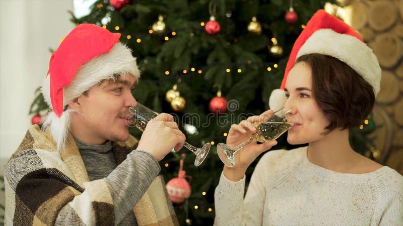 Acclamazioni, fine su per le coppie amorose in vetri tintinnanti del cappello di Santa Claus di shampagne sull'albero di Natale d immagini stock libere da diritti