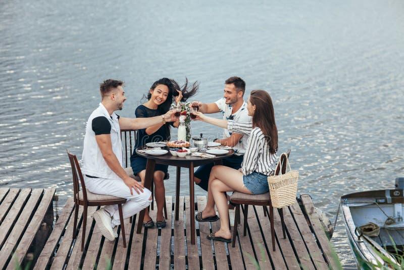 Acclamazioni! Gruppo di amici che godono del picnic all'aperto in pilastro del fiume fotografia stock