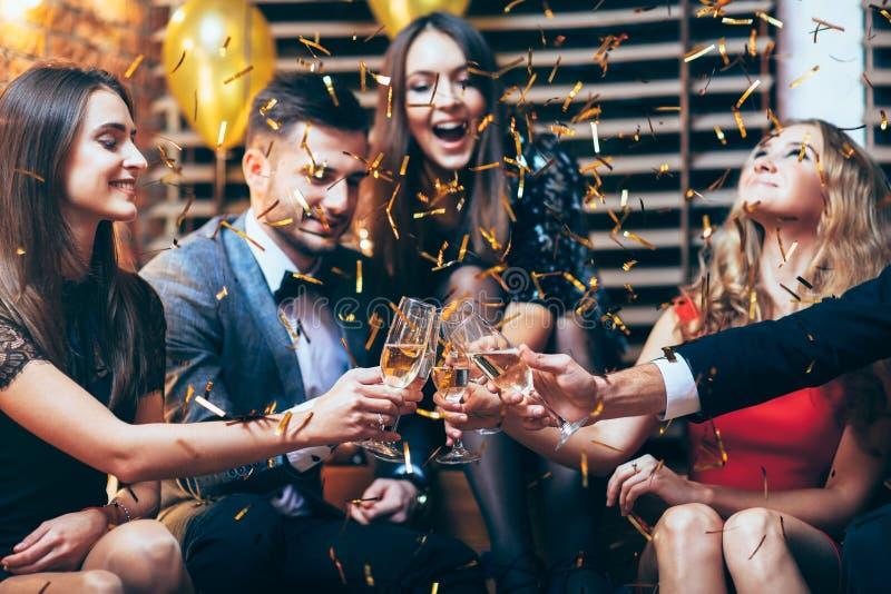 Acclamazioni! Gruppo di vetri tintinnanti degli amici di champagne durante il PA immagine stock