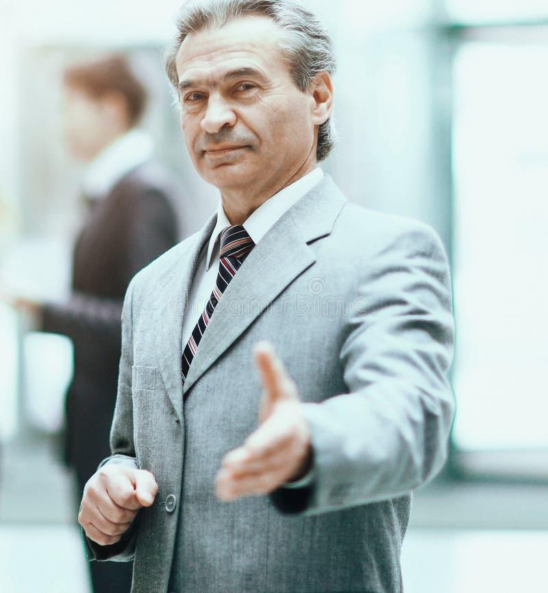 Accogliendo favorevolmente l'uomo di affari pronto alla stretta di mano con la mano estesa, ri immagine stock libera da diritti