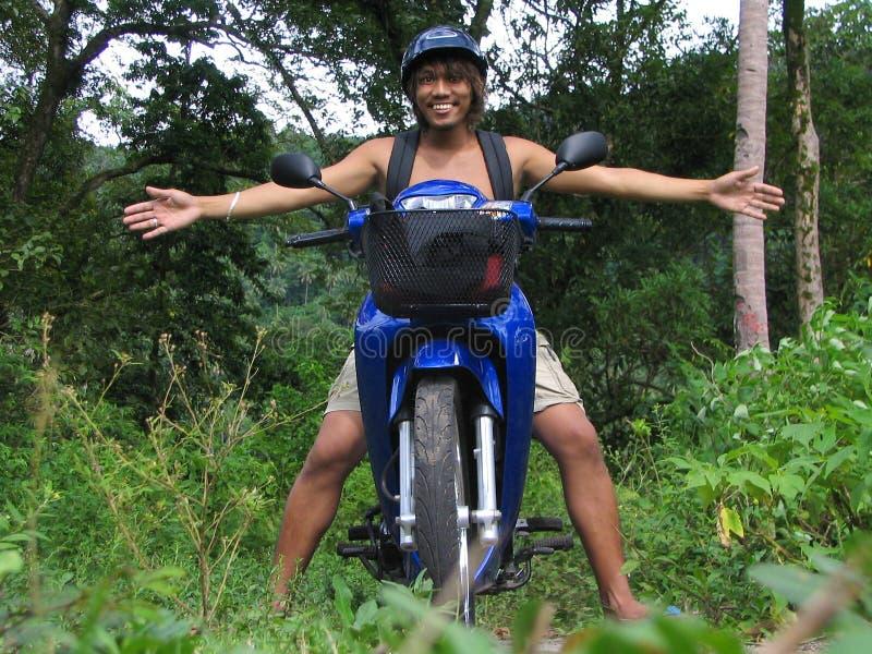 Accogliere favorevolmente ragazzo asiatico sul motociclo immagini stock