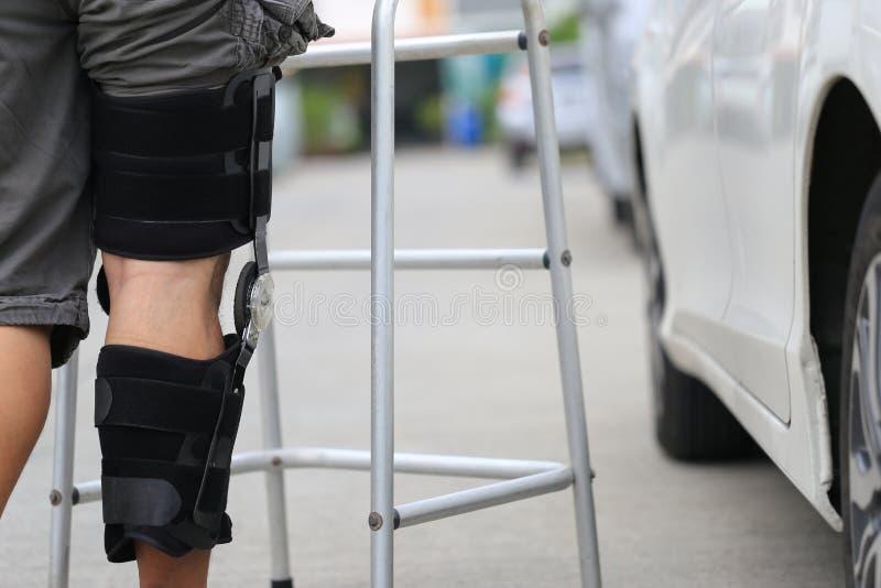 Accolade de soutien de genou d'usage d'homme sup?rieur sur la jambe se tenant au parking de voiture, au concept m?dical et de soi image libre de droits