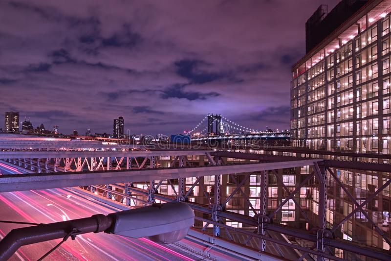 Brooklyn Bridge at Twilight with purple violet hue timing and a well lit building on the right and heavy traffic below royalty free stock photography