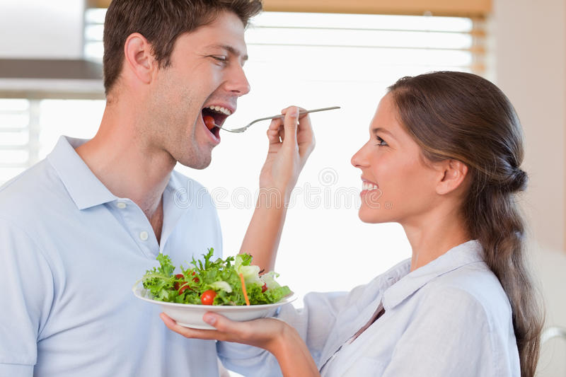 Accomplice couple tasting a salad. In their kitchen royalty free stock photos
