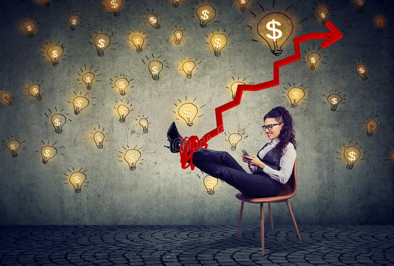 Accomplished business woman relaxing sitting in the office under idea money rain. Young accomplished business woman relaxing sitting in the office under idea royalty free stock photo
