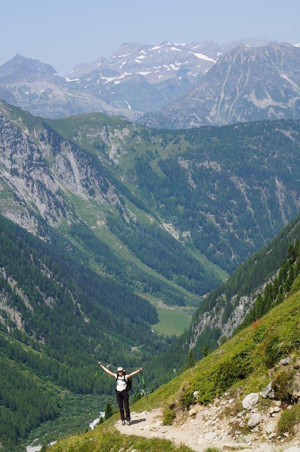 Accomplissement d'un randonneur heureux sur une piste de montagne photo stock