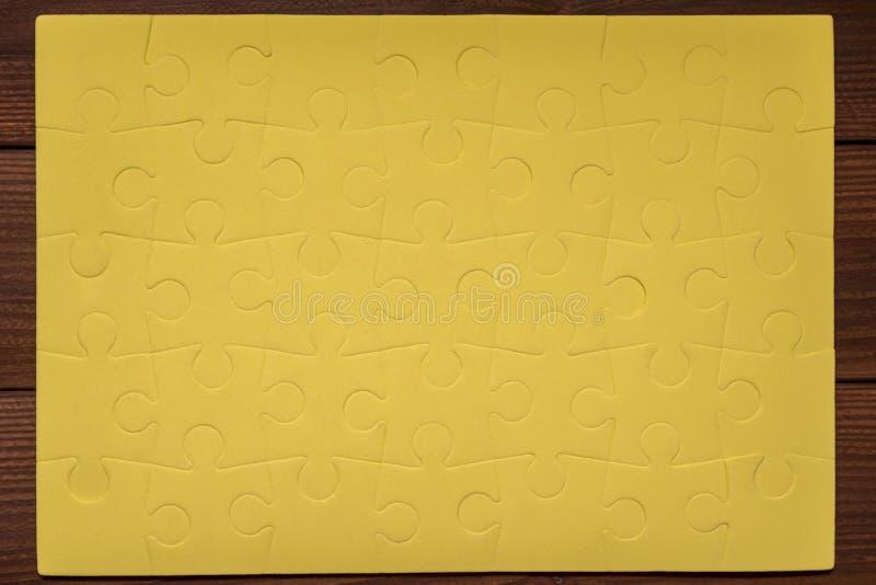 Accomplissez les puzzles jaunes sur la table en bois image stock
