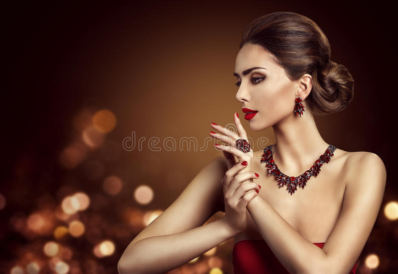 Acconciatura del panino dei capelli della donna, gioielli di Beauty Makeup Red del modello di moda fotografia stock