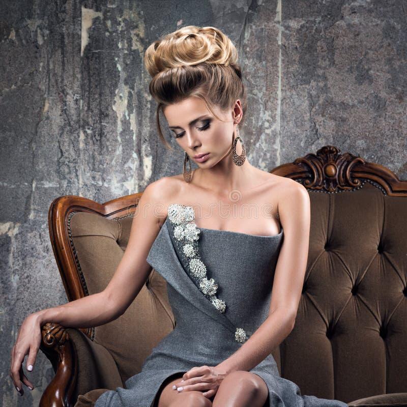 Acconciatura di sera e vestito grigio lussuoso Bella giovane donna fotografia stock