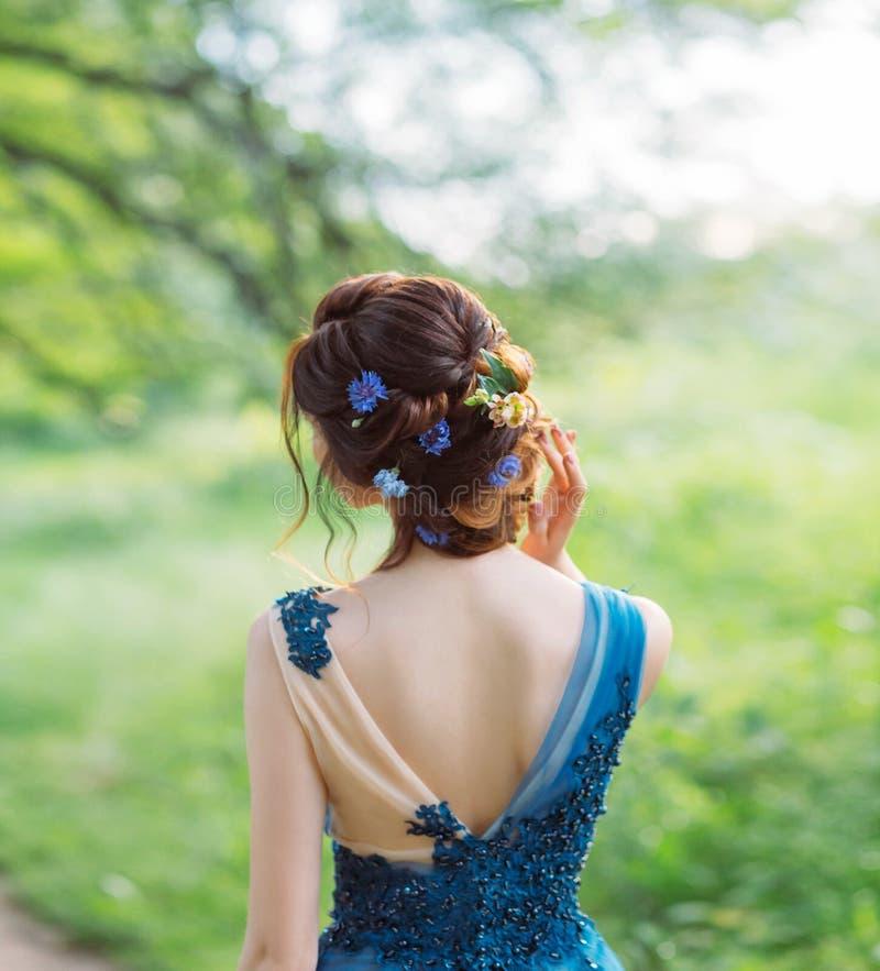 Acconciatura elegante fresca insolita per capelli scuri lunghi, lavoro del parrucchiere, immagine per la graduazione e nozze, cri immagine stock