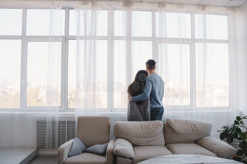 Accoppi abbracciare lo sguardo attraverso la finestra immagine stock