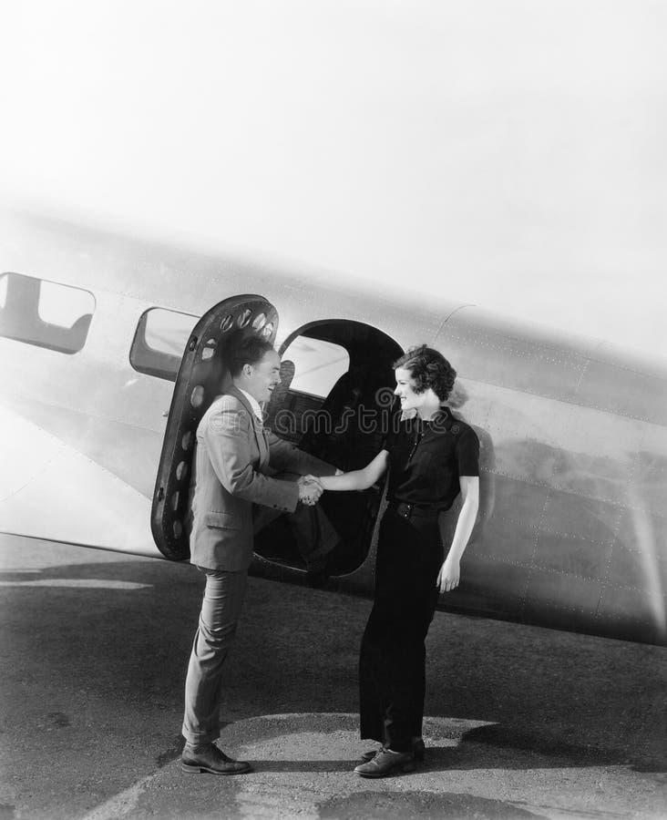 Accoppi accogliersi ad un piccolo aeroplano (tutte le persone rappresentate non sono vivente più lungo e nessuna proprietà esiste fotografia stock