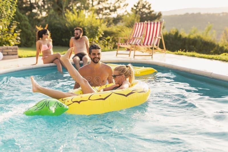 Accoppi alla piscina fotografia stock