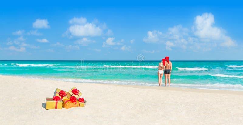Accoppi in cappelli di Santa di Natale alla spiaggia con i regali di festa immagine stock libera da diritti