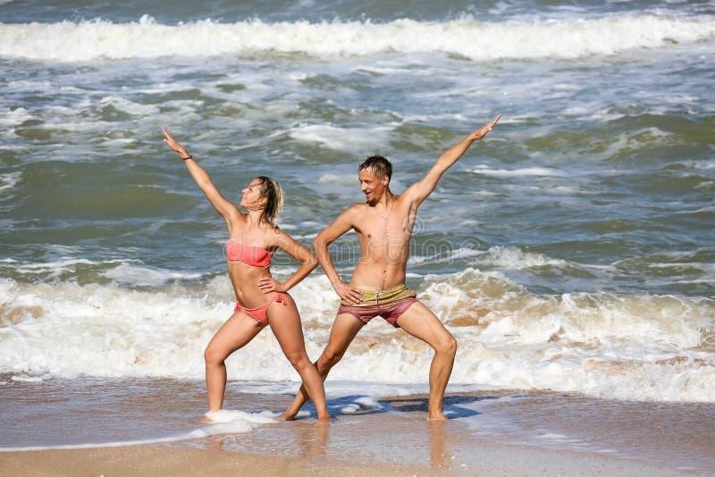 Accoppi degli amanti che ballano dal mare fotografia stock