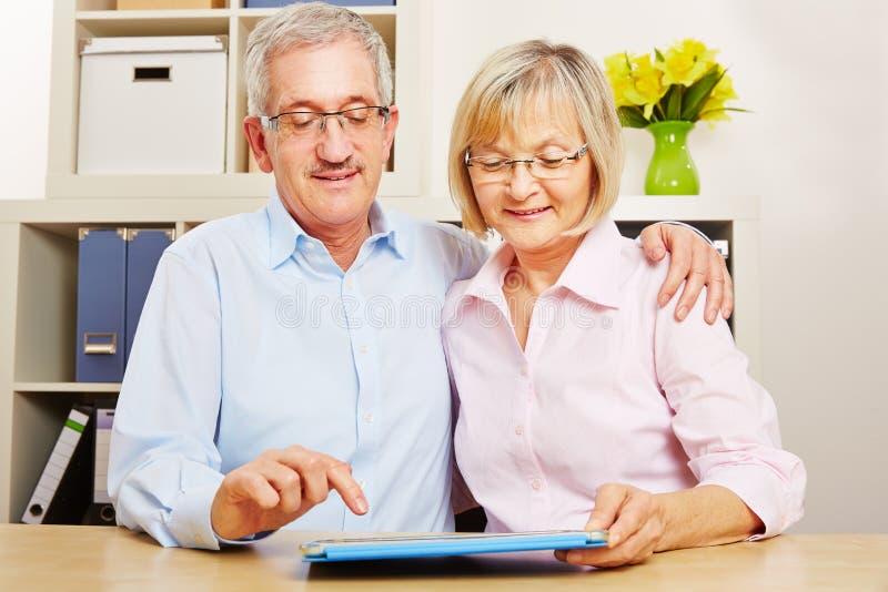 Accoppi degli anziani gioca il app sul computer della compressa immagine stock libera da diritti