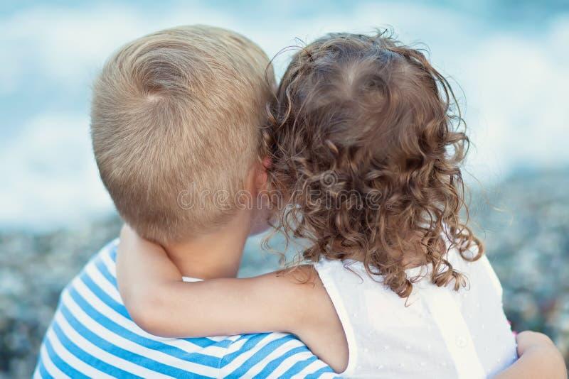 Accoppi dei bambini che mettono sulla spiaggia La bambina abbraccia il ragazzo dalla parte posteriore immagini stock libere da diritti