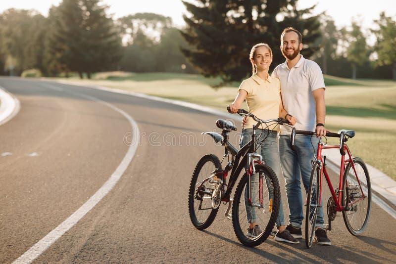 Accoppi dei ciclisti è sorridente ed esaminante la macchina fotografica fotografia stock libera da diritti