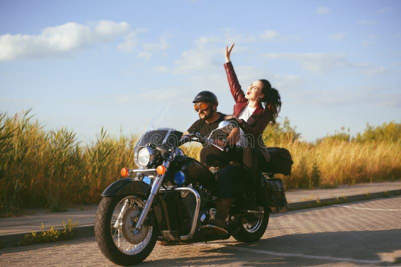 Accoppi dei motociclisti guidano attraverso il campo Un uomo conduce un motociclo, una ragazza ascolta musica con le cuffie sulla fotografie stock
