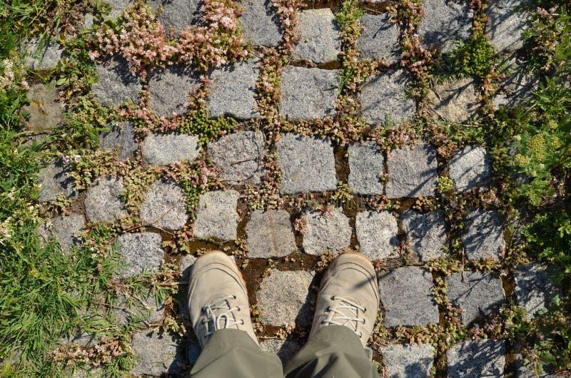 Accoppi dei piedi in scarpe di tela sul marciapiede delle pietre del ciottolo fotografia stock libera da diritti