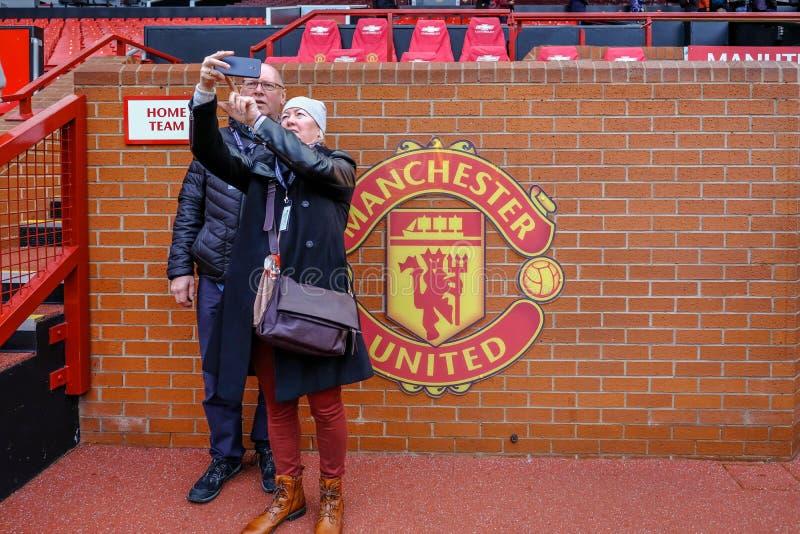 Accoppi dei sostenitori che prendono un selfie davanti al riparo della squadra locale al Manchester United fotografie stock