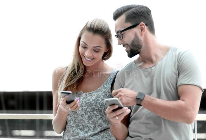 Accoppi dei turisti che esaminano i loro schermi dello smartphone immagini stock libere da diritti