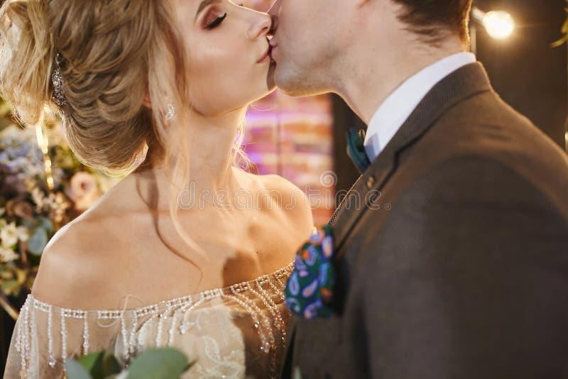 Accoppi di baciare gli amanti, giovane uomo d'affari bello nel vestito alla moda abbraccia la bella ragazza di modello con nozze immagini stock