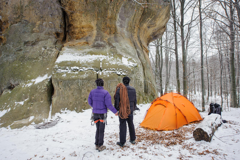Accoppi gli scalatori in un orario invernale vicino al campeggio della montagna immagini stock