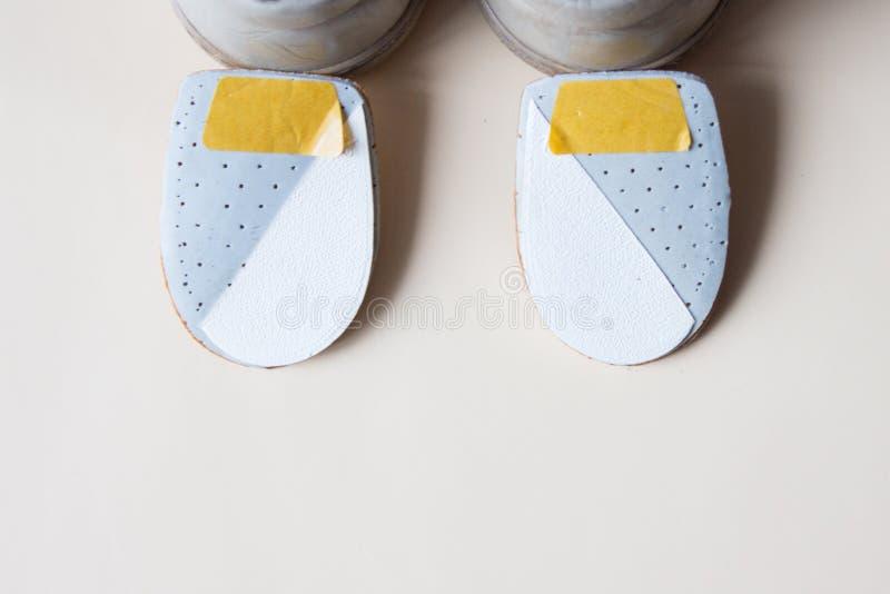 Accoppi i nuovi cuscinetti ortopedici di cuoio del tallone con le scarpe su backg beige fotografia stock libera da diritti