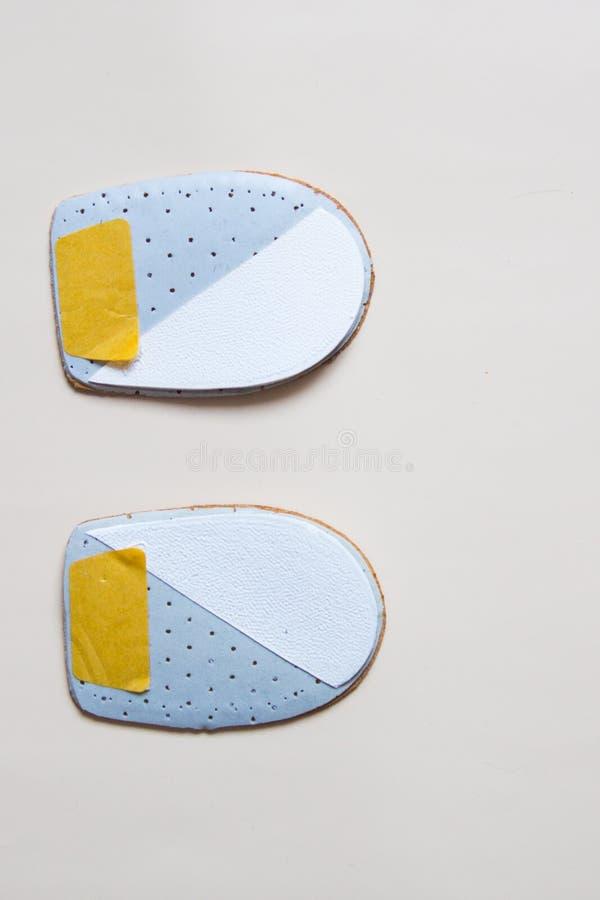 Accoppi i nuovi cuscinetti ortopedici di cuoio del tallone isolati su backgr neutrale immagine stock