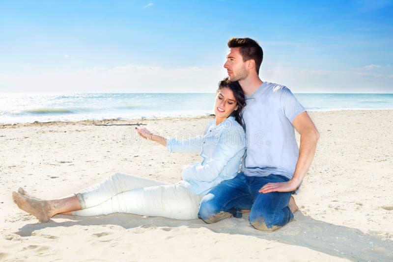 Accoppi il rilassamento sulla sabbia alla spiaggia che guarda il mare fotografia stock