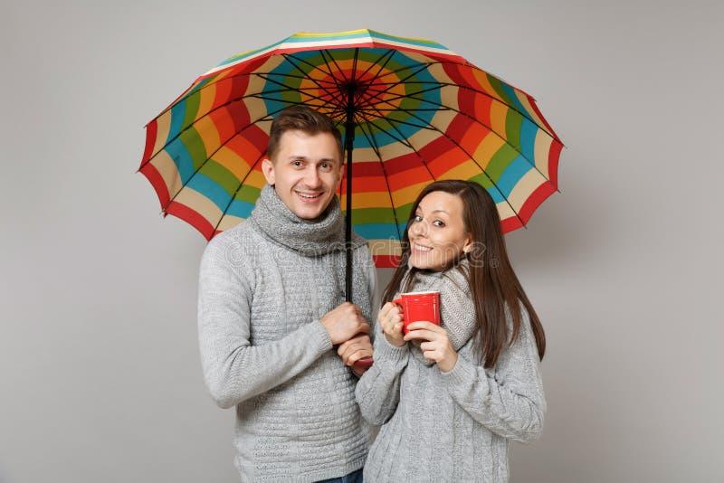 Accoppi insieme il tipo della ragazza in sciarpe grige dei maglioni sotto l'ombrello isolato sul fondo grigio della parete, ritra immagine stock libera da diritti
