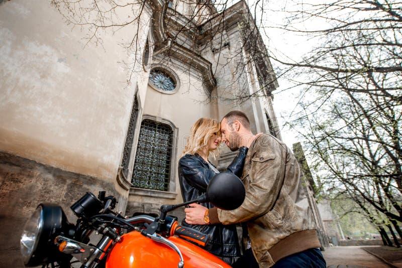 Accoppi l'abbraccio vicino al motociclo sui vecchi precedenti della città immagine stock