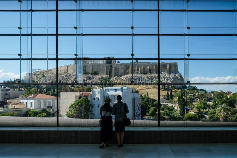 Accoppi l'esame fuori l'acropoli in tutto la finestra di vetro enorme nel museo dell'acropoli Atene, Grecia fotografia stock