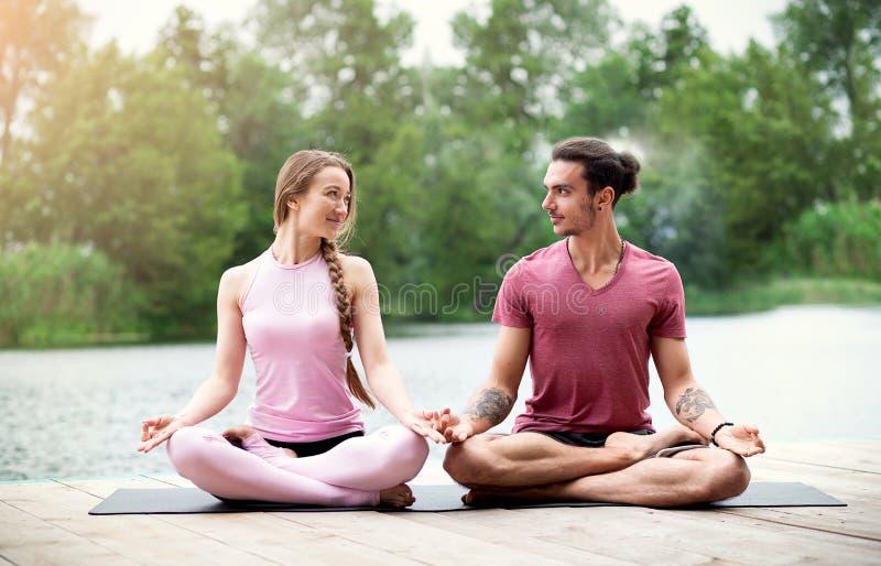 Accoppi l'yoga di pratica e l'esame reciprocamente in natura vicino al fiume Meditazione delle coppie fotografia stock libera da diritti
