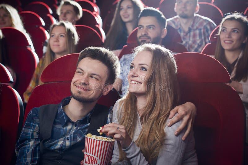 Accoppi la seduta insieme in cinema, guardante la commedia fotografia stock