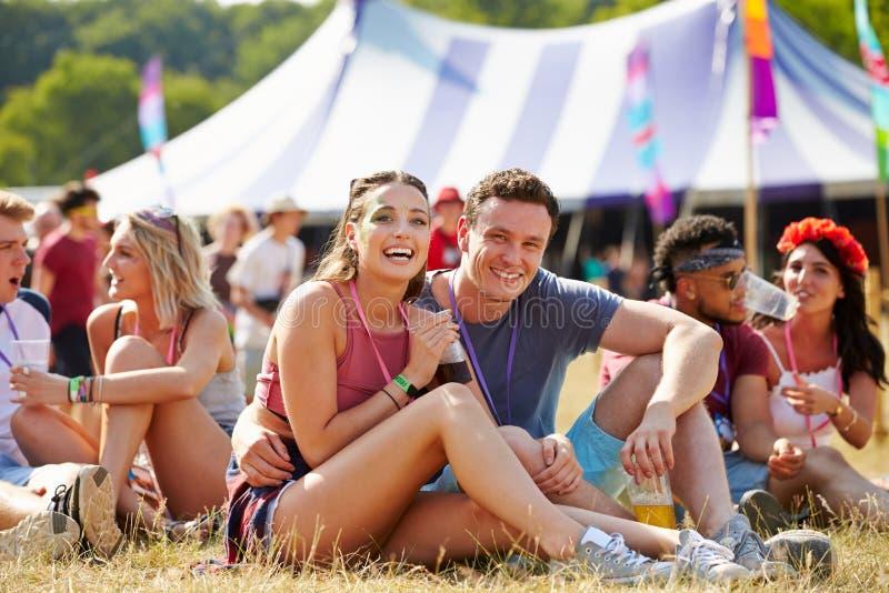 Accoppi la seduta sull'erba nel pubblico ad un festival di musica immagine stock libera da diritti