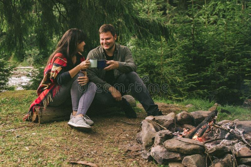 Accoppi la seduta vicino al fuoco del campo ed al tè bevente e raccontare le storie tenda e suv su fondo fotografia stock