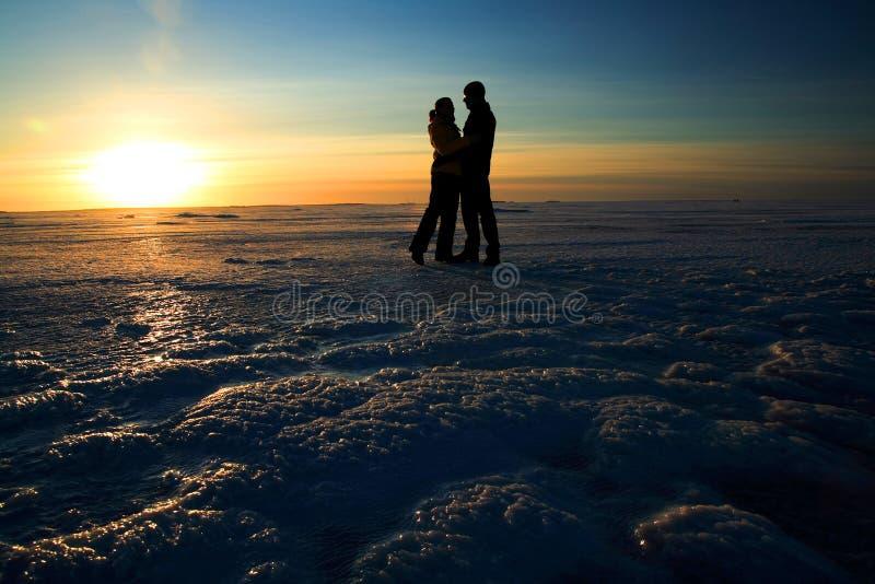 Accoppi le mani della holding contro il tramonto sul mare congelato fotografie stock libere da diritti