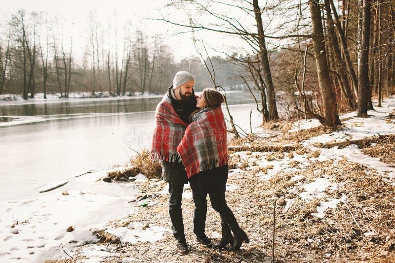Accoppi lo sguardo vicino al lago dell'inverno sotto il plaid fotografia stock libera da diritti
